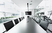 Long table in conference hall with TV, transparent walls