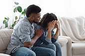 Dependent Relationship. Young Black Guy Soothing His Depressed Girlfriend At Home