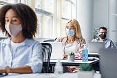 Work of employees of corporate company after coronavirus quarantine. Multiracial workers in protective masks at desks with laptops and antiseptics