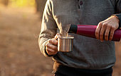 Cropped of man pouring hot tea from thermos in forest