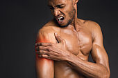 Handsome shirtless black man suffering from pain in arm