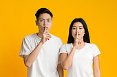 Serious asian couple make silence sign, keep forefingers on lips