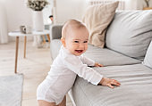 Cute Little Baby Smiling To Camera Standing Near Couch Indoor