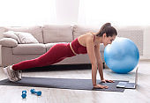 Strength training at home. Fit millennial woman doing plank exercise or push ups to video class in apartment