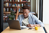Irritated African American guy using laptop to work on difficult business project at city cafe