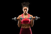 Athletic afro girl having work out with barbells