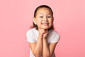 Hopeful little asian girl praying for something