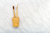Bamboo toothbrushes in hand made clay glass on white marble background. Flat lay with copy space. Biodegradable natural bamboo toothbrush. Eco friendly, Zero waste, Dental care Plastic free concept