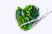 Weight loss diet. Fresh green leaf lettuce, spinach, sorrel, dill and measuring tape on heart shaped plate on white background. Healthy eating. Organic and vegetarian food. Copy space for text