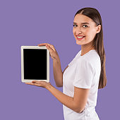 Happy girl showing tablet with blank screen to camera