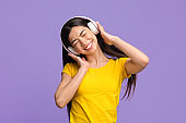 Carefree Mood. Cheerful Asian Woman Enjoying Listening Favorite Music In Wireless Headphones