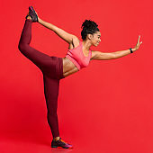 Happy athletic girl in yoga pose over red background