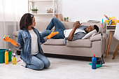 Lazy black man relaxing on sofa with smartphone while wife cleaning flat