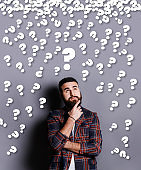 Bearded Caucasian guy looking up and thinking over grey background with question marks, creative collage