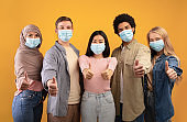 International multi-ethnic student exchange. Young multiracial people in protective masks showing thumbs up
