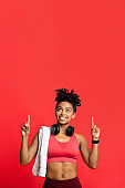 Happy afro sporty girl with towel and earphones pointing up