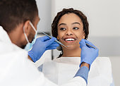 Pretty black lady looking at her dentist with smile
