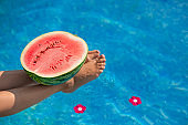 Watermelon in pool on woman slim legs in summer holiday time. Bali Tropical beach luxury lifestyle. Woman relaxing, watermelon and spa flowers in resort blue swimming pool. Foot spa and skin care