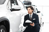 Insurance Agent Sitting Taking Notes About Used Car