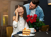 Loving Man Covering Girlfriend's Eyes Giving Her Bouquet In Cafe