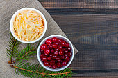 Sauerkraut or fermented cabbage with cranberries on rustic wooden background. The concept of proper nutrition and healthy eating. Organic and vegetarian food contain vitamin c. Flat lay, copy space for text