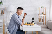 Hobby and online lesson. Young man plays chess and shoots on webcam