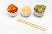 Fermented vegetables, sauerkraut, salty preservation pickles cucumber and tomatoes on white background. Healthy eating. Organic farm vegetarian food. Close up, copy space for text