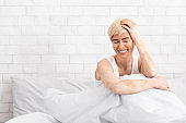 Middle aged woman with vitiligo laughing in bed