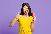Excited Cheerful Asian Woman Holding Credit Card And Showing Thumb Up