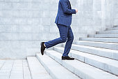 Closeup view of entrepreneur running up stairs, being late for work in busy city