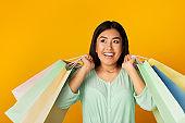Joyful Asian Woman With Shopper Bags Posing Over Yellow Background