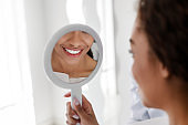 White smile in mirror, african girl visiting dentist
