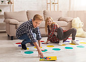 Brother And Sister Having Fun Playing Twister Game On Floor