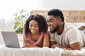 Funny african couple using laptop in bed