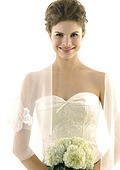 Portrait of a bride holding a bouquet of flowers and smiling