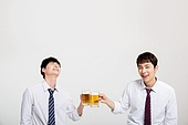 Two cheerful mans holding pints of beer