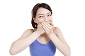 Cute young woman smiling with hands covering mouth