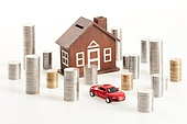 Coins around toy car and model house