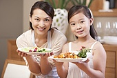 Mother and daughter serving Chinese dishes