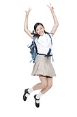Excited schoolgirl jumping and doing victory sign with schoolbag on the back