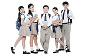 Happy primary school friends with books and schoolbags