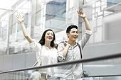 Young couple waving on escalator