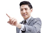 Cheerful young businessman pointing away