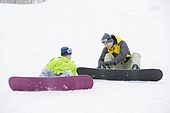 Young father and son with snowboards on the snow