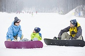 Young parents teaching son to snowboard