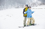 Young man teaching girlfriend to snowboard