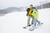 Young father teaching son to snowboard