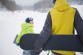 Young father and son walking with snowboards on the snow