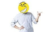 Young man with a happy emoticon face in front of his face