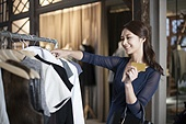 Young woman with credit card in clothing store